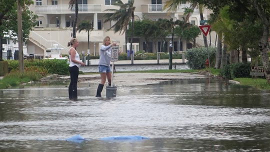 """In this Oct. 5, 2017, file photo, residents move a """"no wake,"""" sign through flood waters caused by king tides in Fort Lauderdale, Fla. Federal scientists predict 40 places in the U.S. will experience higher than normal rates of so-called sunny day flooding this year due to rising sea levels and an abnormal El Nino weather system."""