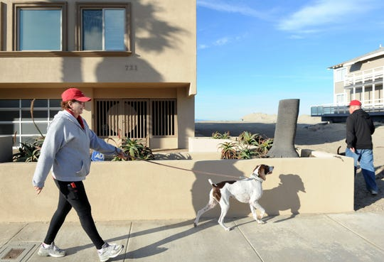 Jackie Baron and her husband Jim are seen walking their dogs in this 2016 photo at Oxnard Shores. The neighborhood for years has been divided over the issues of short-term rentals.