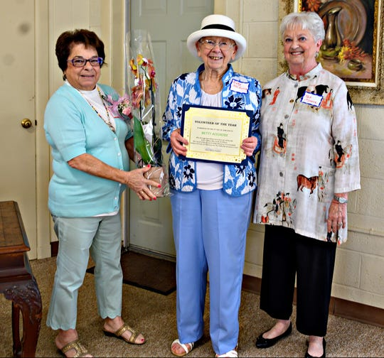 Pam McNamee (from left), awards chairperson, Millville Woman's Club, presents flowers to Betty Aleshire, the club's Volunteer of the Year, as Pat Moore, club president, looks on.