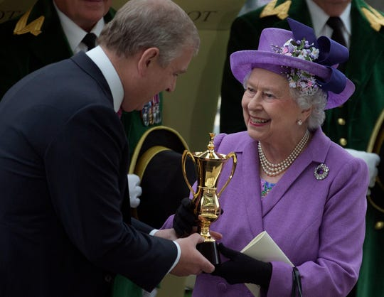 Prince Andrew, the Duke of York, affords his mom, Queen Elizabeth II, with a trophy after her horse Estimate won the Gold Cup at Royal Ascot in June 2013.