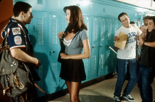 "Jim (Jason Biggs, left) is shocked when beautiful exchange student Nadia (Shannon Elizabeth) asks for help with her studies, while his friends Oz (Chris Klein) and Kevin (Thomas Ian Nicholas, right) look on  in this scene from ""American Pie."""