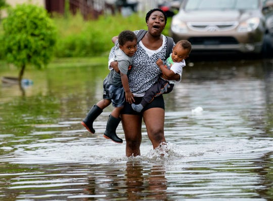 Terrian Jones reacts as she feels something moving in the water at her feet as she carries Drew and Chance Furlough to their mother on Belfast Street in New Orleans during flooding from a storm in the Gulf Mexico that dumped lots of rain Wednesday, July 10, 2019.