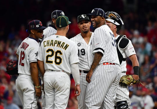 CC Sabathia visits American League pitcher Aroldis Chapman in the ninth inning.