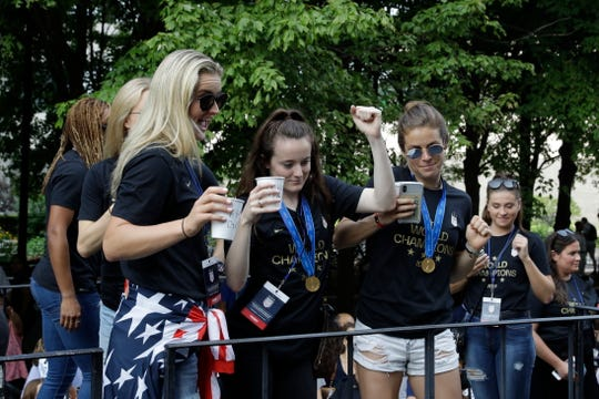 U.S. women's soccer team player Rose Lavelle, center, celebrates while standing with teammates on a float.