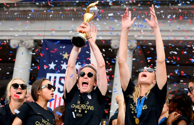 "USA women's soccer player Megan Rapinoe (C) and other team members celebrate with the trophy in front of the City Hall after the ticker tape parade for the women's World Cup champions on July 10, 2019 in New York. - Tens of thousands of fans are poised to pack the streets of New York on Wednesday to salute the World Cup-winning US women's team in a ticker-tape parade. Four years after roaring fans lined the route of Lower Manhattan's fabled ""Canyon of Heroes"" to cheer the US women winning the 2015 World Cup, the Big Apple is poised for another raucous celebration."
