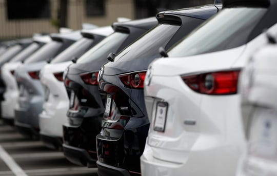 In this May 19, 2019, photo a line of unsold 2019 CX-5 sports-utility vehicles sits at a Mazda dealership in Littleton, Colo.