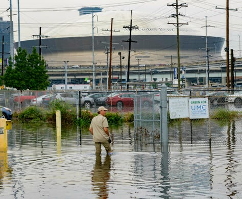 Frank Conforto Jr. walks in the parking lot of the University Medical Center with the Mercedes-Benz Superdome in the background on Glavez Street in New Orleans after flooding from a storm Wednesday, July 10, 2019. Louisiana Gov. John Bel Edwards has declared a state of emergency in anticipation of tropical weather that could dump as much as 15 inches of rain in the state over the coming days.