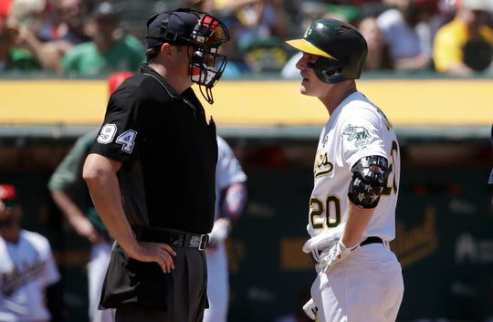 Oakland Athletics' Mark Canha, right, argues with umpire Lance Barrett after striking out against the Minnesota Twins during the fourth inning of a baseball game in Oakland, Calif., Thursday, July 4, 2019. (AP Photo/Jeff Chiu) ORG XMIT: OAS110