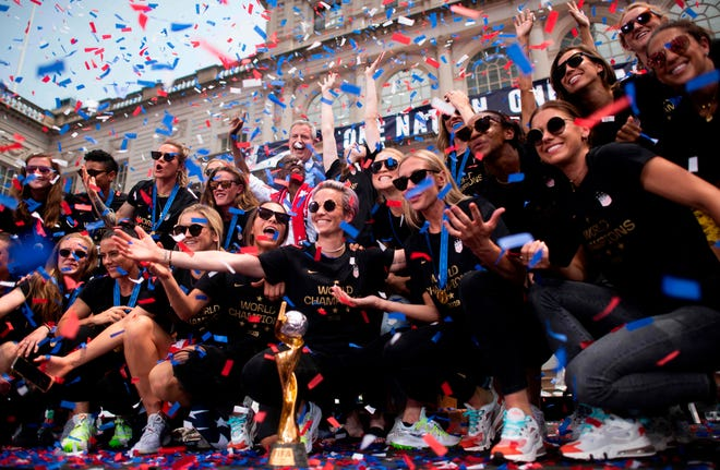 """Members of the World Cup-winning US women's team take part in a ticker tape parade for the women's World Cup champions on July 10, 2019 in New York. - Tens of thousands of fans are poised to pack the streets of New York on Wednesday to salute the World Cup-winning US women's team in a ticker-tape parade. Four years after roaring fans lined the route of Lower Manhattan's fabled """"Canyon of Heroes"""" to cheer the US women winning the 2015 World Cup, the Big Apple is poised for another raucous celebration."""