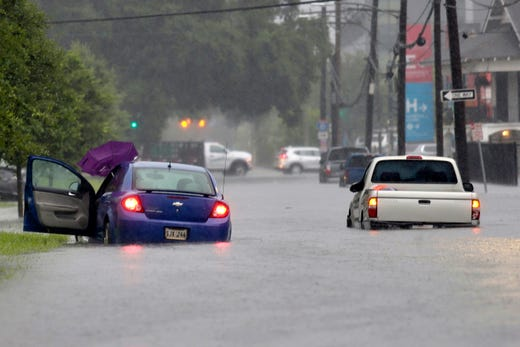 Vehicles are stuck in floodwaters along S. Galvez Street as heavy rain falls, Wednesday, July 10, 2019, in New Orleans.