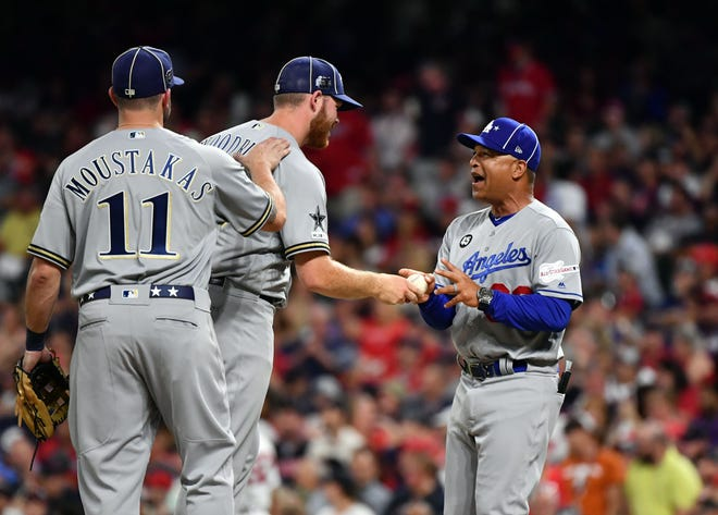 Dave Roberts of the Dodgers relieves Brandon Woodruff (53) of the Brewers during the seventh inning.