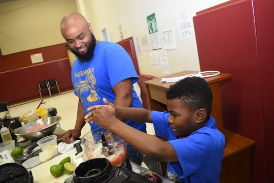John Belvin Jr., executive chef at the Diamond Grill, watches Dorian Hinkston as he squeezes lime juice into a batch of homemade salsa. Belvin was the guest speaker at the Healthy Heroes Camp sponsored and coordinated by the Pineville Rotary Club and the Pineville Youth Center. He taught the campers how to make turkey tacos, homemade salsa and homemade guacamole.