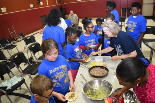 """The Healthy Heroes Camp, sponsored and coordinated by the PIneville Rotary Club along with the Pineville Youth Center, concluded the four-day camp Thursday, July 11, 2019.""""We have about 70 children that registered for the camp,"""" said Christy Frederic, a charter member of the club. Campers were treated to lunch and a program.On Thursday, John Belvin Jr., executive chef of the Diamond Grill, taught the campers how to make Turkey Tacos.""""Today I chose to do some ground turkey tacos with some corn tortillas, homemade guacamole, homemade salsa - just trying to show the kids that it's not boring to eat healthy,"""" said Belvin. The recipe is simple and the children can make at home.Belvin also shared his experiences in the culinary field and his life with the campers.Dorian Hinkston, 6 - but will """"turn 7 in a few days"""" - was Belvin's helper. He helped sprinkle the seasoning on the ground turkey and said he liked the taste of the seasoning.Dorian said he wanted to be a chef when he grew up.""""Because I want people to like my food that I make,"""" he explained."""