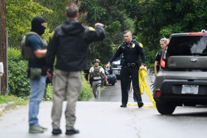 Police walk along Reed Street in Shiloh July 11, 2019 as they work to take a male suspect into custody in connection to a shooting.