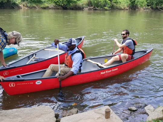 N.C. Department of Natural Resources Secretary Michael Regan pilots a canoe July 10 on the French Broad River with Hartwell Carson, French Broad Riverkeeper. Derek Turno, owner of French Broad Outfitters, far left, guides the boat into a landing.