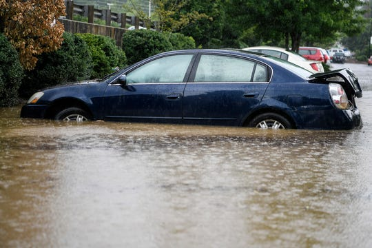 Cars were submerged in water in a plaza parking lot on Merrimon Avenue in North Asheville after heavy rain swept through the area July 11, 2019.