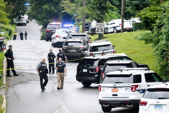 Police walk along Reed Street in Shiloh July 11, 2019 as they work to take a male suspect into custody.