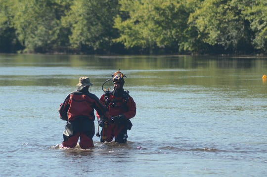 Deputy Scott Ware, right, and Deputy Brian Hansford of the Barry County Sheriff Department dive team recover some dynamite from the Kalamazoo River during a Thursday training exercise.