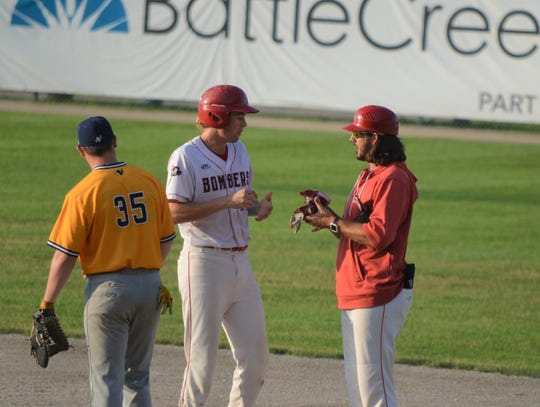 Battle Creek Bombers coach talks to a player at first base. The Bombers Hitting Coach, Zach Gartner played for the team last year and was an All-Star before getting into coaching.