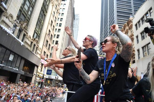 Ashlyn Harris, in foreground, of Satellite Beach and Megan Rapinoe, behind her. take part in the U,S, women's soccer team's ticker tape parade in New York.
