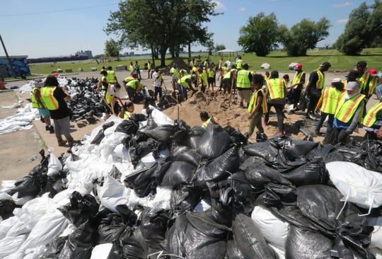 Volunteers fill sandbags at Alfred Brush Park to place along canals in the Jefferson Chalmers neighborhood. The area is being flooded by the rising Detroit River Thursday, July 11, 2019 in Detroit, Mich.