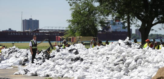 Volunteers palsied sandbags along canals in the Jefferson Chalmers neighborhood to hold back the rising Detroit River Thursday, July 11, 2019 in Detroit, Mich.