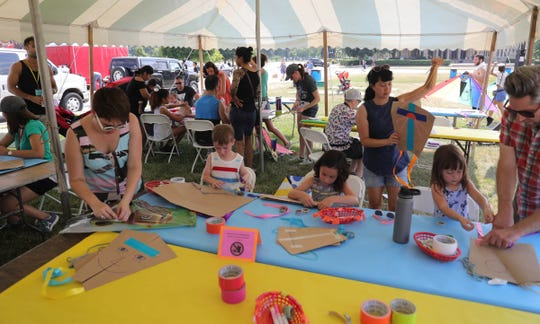 Kids work on their kites during Detroit Kite Festival on Belle Isle Sunday, July 15, 2018. Kite enthusiasts from all over Metro Detroit enjoyed the festivities.