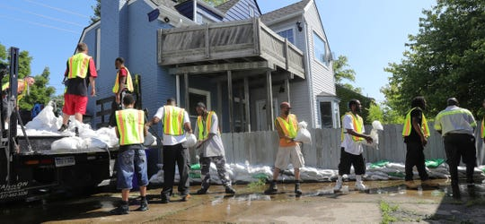 Volunteers place sandbags along canals in the Jefferson Chalmers neighborhood. The area is being flooded by the rising Detroit River Thursday, July 11, 2019 in Detroit, Mich.