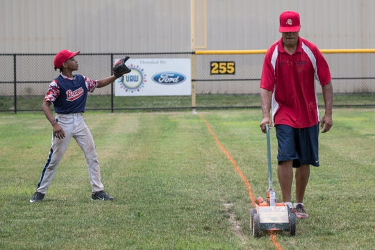 Garrett Street, head coach of Detroit Braves, right, marks the third base line as Zion Finley, 10, practices at Balduck Park in Detroit, Saturday, July 6, 2019.