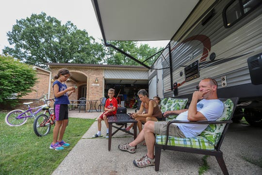 The Rende family sits outside their travel trailer parked in the driveway of their home in Troy. The family has been living in the trailer since May.