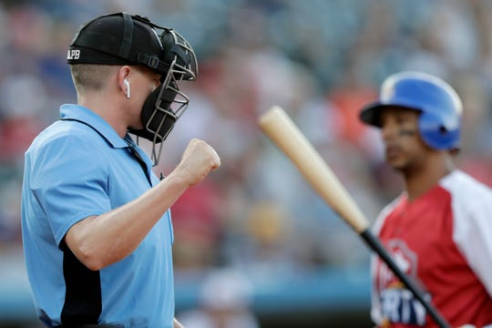 Home plate umpire Brian deBrauwere, left, calls a strike given to him by a radar system over an earpiece as Liberty Division's Tyler Ladendorf, right, strikes out during the first inning of the Atlantic League All-Star game on Wednesday.