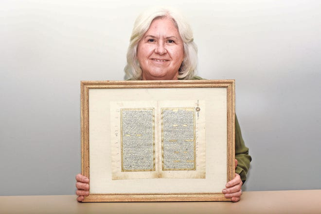 Judy Mattila with her framed pages from a book.