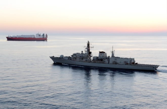 In this image from file video provided by UK Ministry of Defence, British navy vessel HMS Montrose escorts another ship during a mission to remove chemical weapons from Syria at sea off coast of Cyprus in February 2014. The British Navy said it intercepted an attempt on Thursday, July 11, 2019, by three Iranian paramilitary vessels to impede the passage of a British commercial vessel.