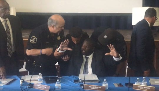 Police officers remove police commissioner Willie Burton from a board meeting where facial recognition software was discussed