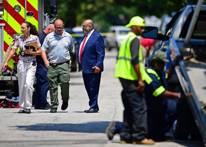 Police officers walk to the crime scene, Tuesday, July 9, 2019, in Cleveland. Police investigating the shooting death of a man in a vacant lot say they also found the bodies of a woman and two children in a nearby house. Authorities aren't saying how the three found inside the house Tuesday died, but they did say the four deaths are connected.