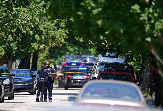 Police officers tape off the crime scene where several bodies were found, as two vehicles are towed away, Tuesday, July 9, 2019, in Cleveland.