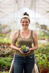 Rachel Nisch, owner of Graye's Greenhouse in Plymouth, holds a container garden that includes kalanchoe, haworthia, sedum, and echeveria.