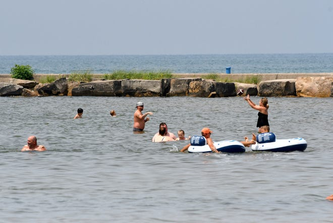 Swimmers and sunbathers enjoy a day at the beach on Lake Michigan at Ludington on Thursday, July 5, 2018. Western Michigan counties along Lake Michigan have been issued warnings against swimming in the lake due to the potential for high waves and rip currents.