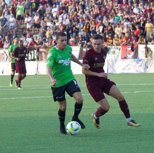 FC Juarez midfield Mauro Fernandez shields the ball from Detroit City FC's Danny Deakin in the first half Wednesday.
