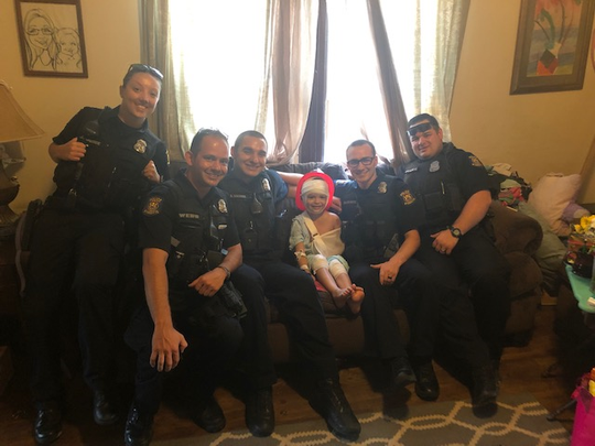Wyandotte police officers visit a girl injured in a crash with a motorcyclist who was allegedly fleeing police.