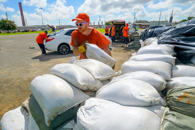 St. Bernard Parish Sheriff's Office inmate workers move free sandbags for residents in Chalmette, La., Thursday, July 11, 2019.