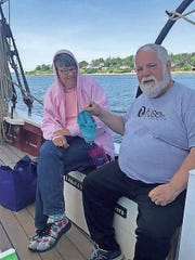 Barb Caddy with her husband, Mark, as he holds up her cowl knitting project aboard the Schooner J&E Riggin.