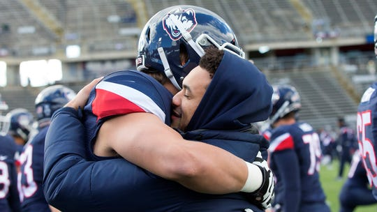 Eli Thomas, right, hugs teammate AJ Garson after returning to UConn as an honorary captain against SMU on Nov. 10, 2018.