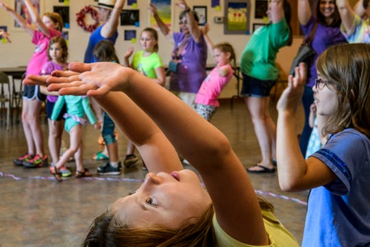 Caroline Delano, bottom, stretches her arms back as far as they can go while dancing with other Art Garden Week II summer camp participants at Patchwork Central in Evansville, Ind., Wednesday, July 10, 2019. Children learned about gardening through art, storytelling and preparing healthy foods on Monday through Thursday mornings.