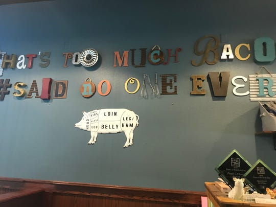 "A wall at The Sweet & Salty Pig reads ""That's too much bacon. #Said no one ever."""