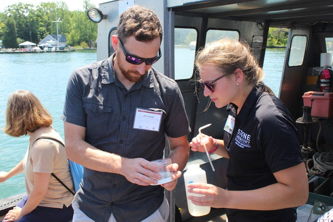 Jim Hood, assistant professor in the aquatic ecology lab at Ohio State University, shows a water sample from Lake Erie to Stone Lab biological field station assistant Emily Fulk Thursday aboard one of Ohio Sea Grant and Stone Laboratory research vessels.