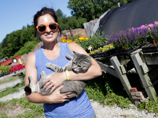 Lindsay Hendricks, assistant director of horticulture at the Green Bay Botanical Garden, holds Sunny, a stray cat who was found on the property in 2016 and has been cared for by the staff ever since. Sarah Kloepping/USA TODAY NETWORK-Wisconsin