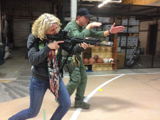 Amber Pinski learns how to walk with Great Falls Police Department Officer Scott Bambenek's firearm during a Citizens' Academy presentation a few years ago. The GFPD is accepting applications for its 24th academy, and the Cascade County Sheriff's Office is offering its first class.