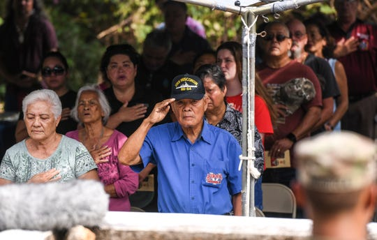 World War II survivor, Vicente Angoco, salutes posted flags during the singing of the national anthem, as he and others attend the first Asinan Memorial Ceremony held at the Yona-Chalan Pago Bridge on Thursday, July 11, 2019.
