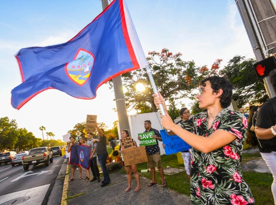 Maite resident Edward Leon Guerrero waves a Guam flag in the air as he joins Prutehi Litekyan, or Protect Ritidian, members and other grassroot supporters during a protest to raise awareness of cultural and environmental concerns, regarding the military buildup, at the Paseo Loop in Hågatña, on Wednesday, July 10, 2019.